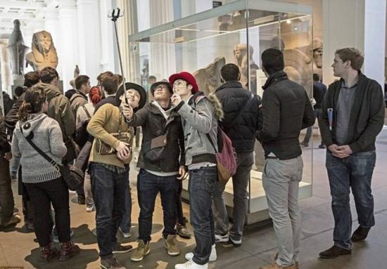 Visitantes tiram foto usando pau da selfie no National Gallery, em Londres. Atitude agora é proibida.
