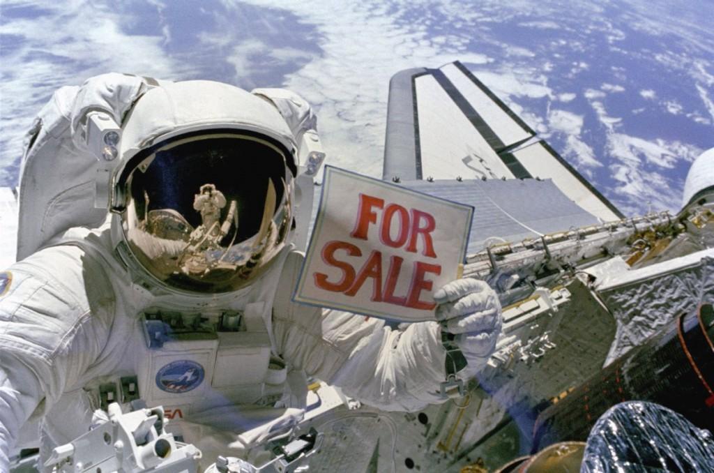"""Em 14 de novembro de 1984, o astronauta Dale A. Gardner segura uma placa """"For Sale"""" (À Venda, en inglês) referindo-se adois satélites, Palapa B-2 e Westar 6. Não deixa de parecer também uma piada, já que nosso planeta está ao fundo. O astronauta Joseph P. Allen IV é refletido na viseira do capacete de Gardner."""