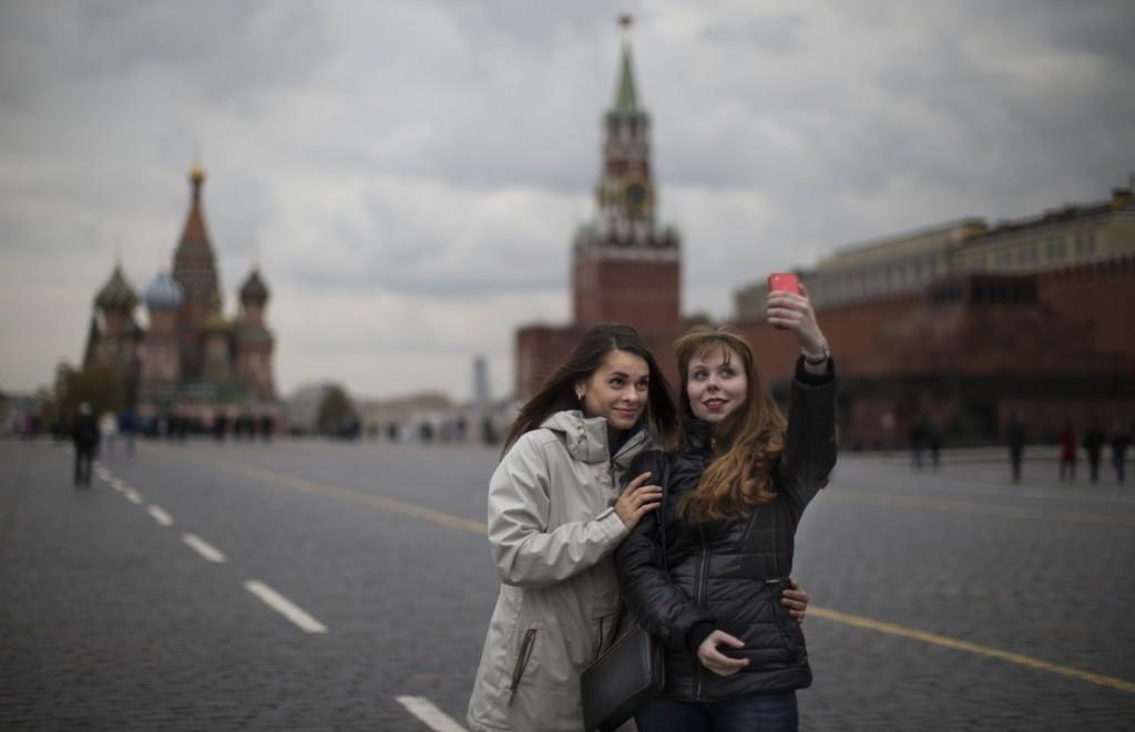 Duas jovens fazem selfie na Praça Vermelha, em Moscou | Foto: Alexander Zemlianichenko/AP