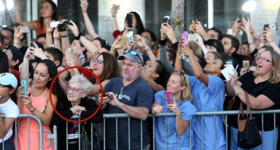 Idosa observa atores enquanto público tenta fotografá-los. | Foto: John Blanding/The Boston Globe