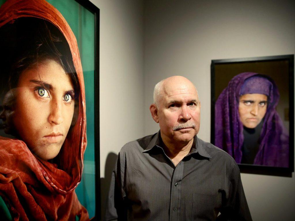 O fotógrafo Steve McCurry entre as duas fotos que fez de Sharbat Gula, uma quando ela era criança e anos depois quando a reencontrou adulta | Foto: Getty